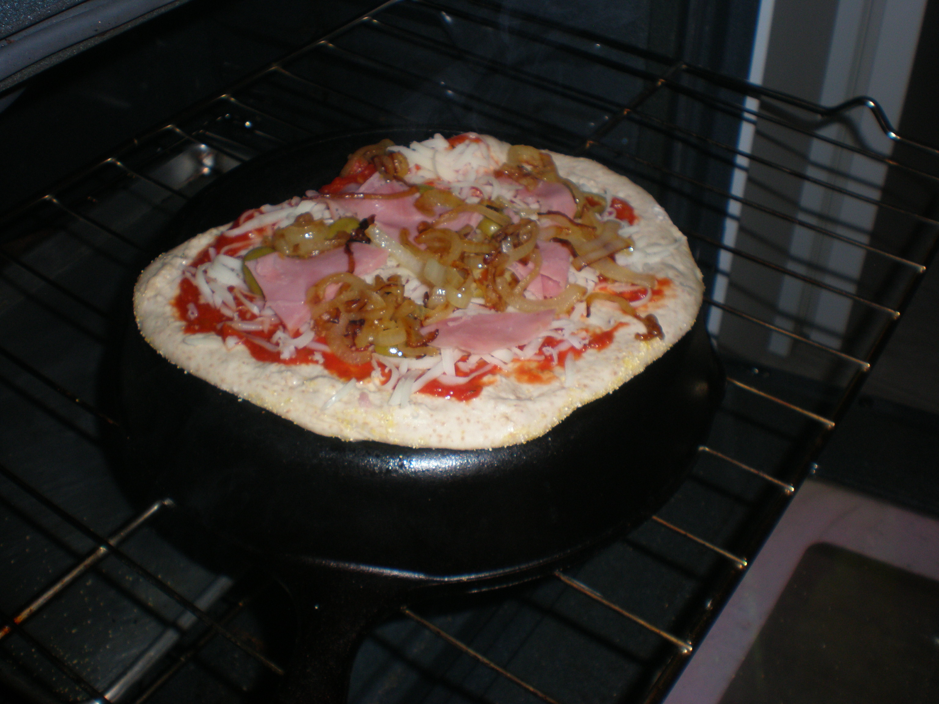 Pizza cooking on the bottom of cast iron pan